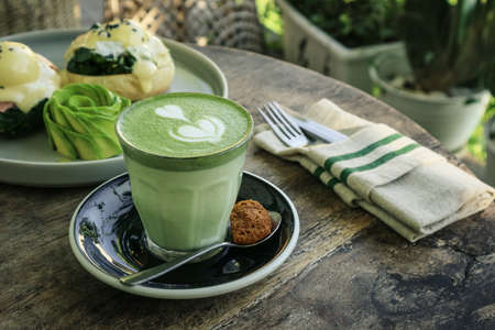 Matcha latte with latte art on top on a wooden background closeup Foto de archivo - 154473993