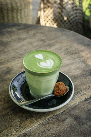 Matcha latte with latte art on top on a wooden background closeup