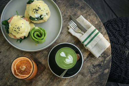 Avocado toast with poached egg, matcha latte and orange juice for breackfast, top view