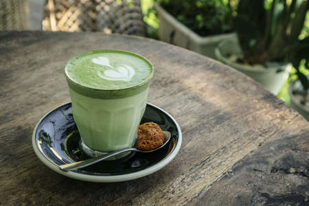 Matcha latte with latte art on top on a wooden background closeup Foto de archivo - 154474019
