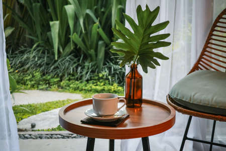 Beautiful tropical terrace or balcony with small table, chair and coffee Foto de archivo