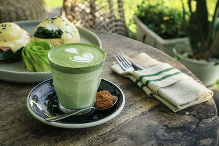 Matcha latte with latte art on top on a wooden background closeup Foto de archivo - 154474028