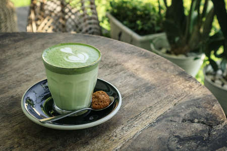 Matcha latte with latte art on top on a wooden background closeup Foto de archivo - 154474031