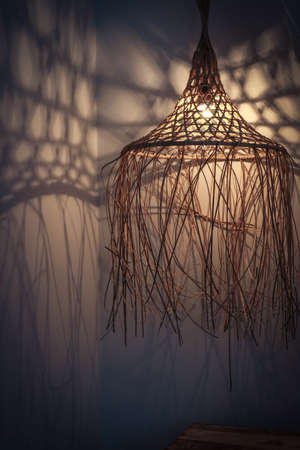 Bamboo lamp in modern boho, tropical , bohemian style with shadows on the wall
