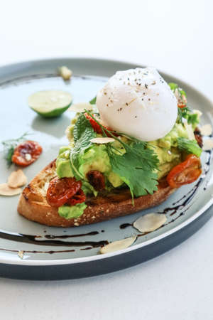 Avocado toast with poached egg, salad leves and cherry tomato for breackfast closeup