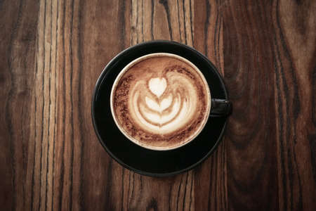 A cup of coffee with latte art on top on wooden table, top view Foto de archivo - 154474057