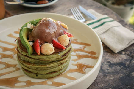 Avocado pancakes with fresh banana, strawberry and ice cream on wooden table closeup