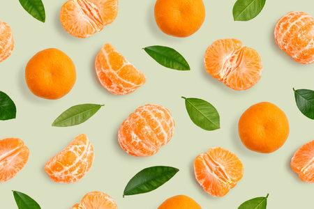 Seamless Pattern of whole  tangerines or mandarin orange fruits, peeled segments and leaves  on green background Standard-Bild