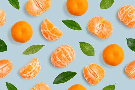 Seamless Pattern of whole  tangerines or mandarin orange fruits, peeled segments and leaves  on light blue background