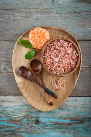 Himalayan pink salt in wooden bowl on wooden background, top view