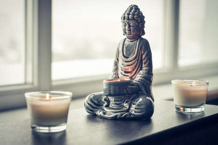 Candlestick in the shape of a buddha, smoldering Palo Santo and burning candles in glass on an wooden table in home interior closeup.