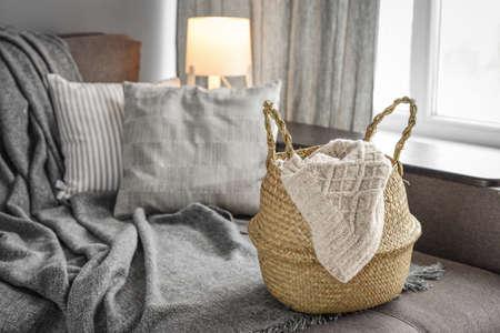 Straw wicker basket with knitting on sofa in interior. Bamboo basket stylish interior item eco design handmade. Decor of home. Standard-Bild