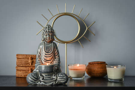 Traditional balinese woven rattan boxes, mirror and buddha statuette  as home decoration on blue background Standard-Bild
