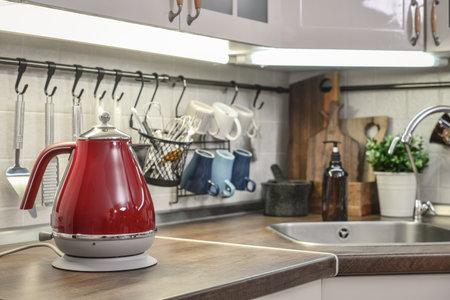 Red electric kettle in retro slile in kitchen interior closeup