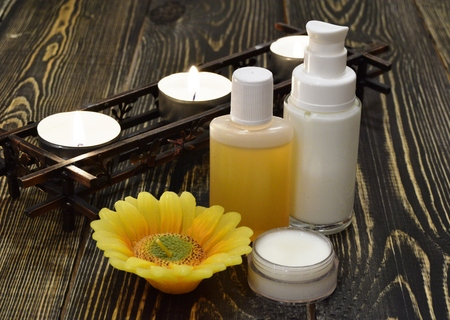 Body cosmetics with candles on wooden background