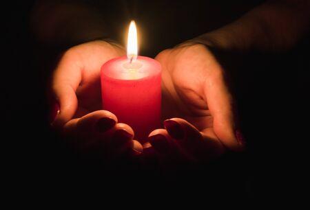Kobiece ręce trzymające płonącą świecę w ciemności