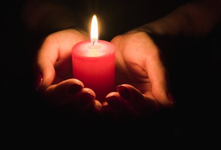 Mains femelles tenant une bougie allumée dans l'obscurité
