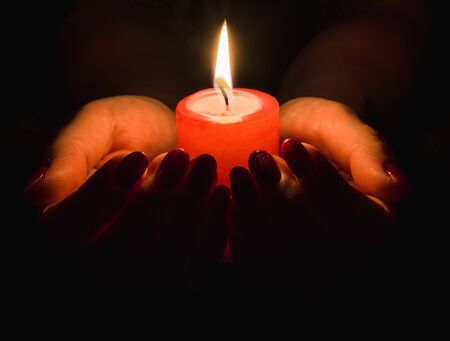 Female hands holding a burning candle in the dark Stock Photo