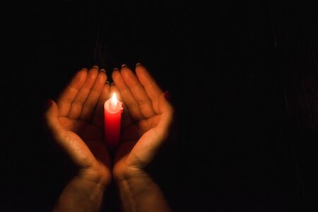 Female hands holding a burning candle in the darkness, hugging it around 스톡 콘텐츠