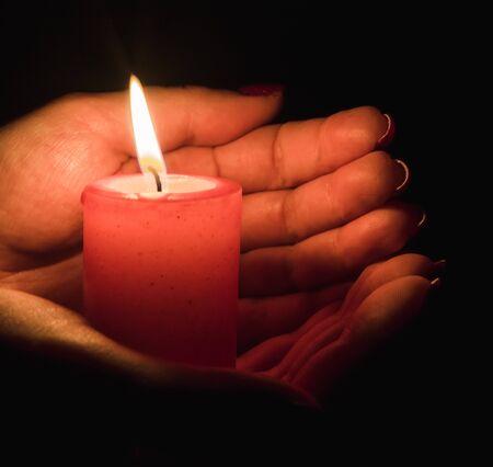 Vrouwelijke handen met een brandende kaars in het donker