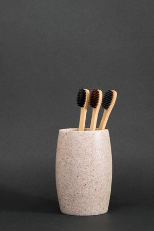 Bamboo eco toothbrushes in a glass on gray background 스톡 콘텐츠