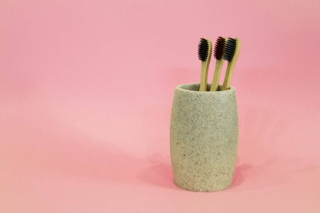 Bamboo eco toothbrushes in a glass on pink background 스톡 콘텐츠