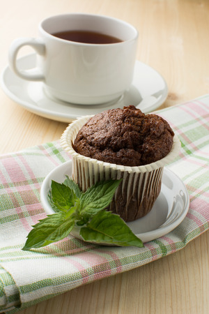 tea light: Chocolate muffin on white dish with sprig of mint linen napkin and a cap of tea. Selective focus