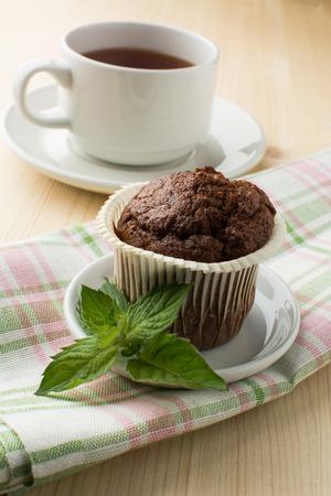 tazza di th�: muffin al cioccolato sul piatto bianco con un rametto di menta tovagliolo di lino e un berretto di t�. messa a fuoco selettiva