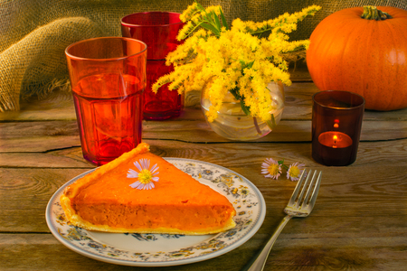 candleholder: Pumpkin pie slice, fork, plate, vase, yellow flowers, mimosa purple daisies, red glasses, candleholder, sackcloth, wood background
