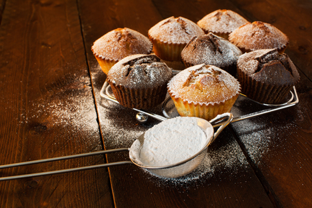 caster: Vanilla and chocolate muffins, caster sugar, sieve for a baking on a dark wooden background, selective focus