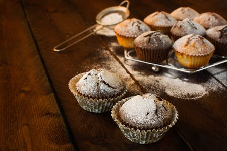 caster: Muffins, caster sugar, sieve for a baking on a dark wooden background, selective focus