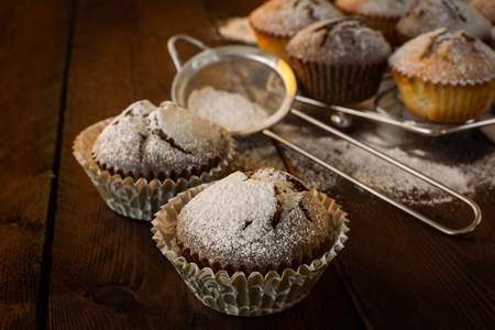 caster: Vanilla and chocolate muffins, caster sugar, sieve for a baking on a dark background, selective focus, copyspace Stock Photo