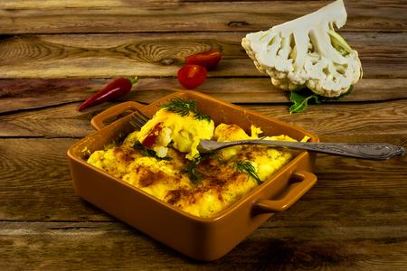 chiles picantes: Al horno coliflor rebozada con queso en una fuente para horno de cerámica cuadrada, tenedor, tomates, pimientos picantes, fondo de madera, horizontal