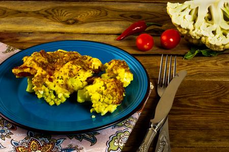 chiles picantes: Coliflor cocida al horno con migas de pan con queso en un plato azul, tenedor, cuchillo, servilleta, tomates, pimientos picantes, fondo de madera, horizontal