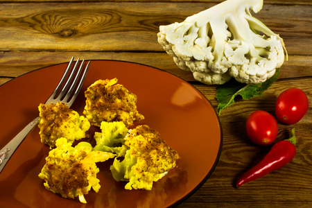 chiles picantes: Baked cauliflower in breadcrumbs with cheese on a brown plate, fork, tomatoes, hot peppers, wooden background, horizontal