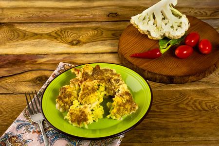 chiles picantes: Horneados au coliflor gratinado con queso en un plato verde, redondo tabla de madera, tomates, pimientos picantes, horizontal
