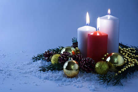 blue candles: Glowing white and red Christmas candles, golden balls, fir branches and cones in snow on a light blue background