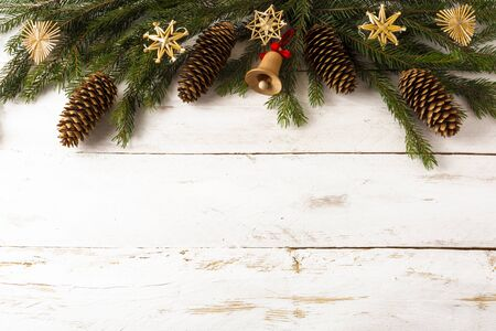 Christmas background decoration fir branches, straw ornaments, wooden jingle bell, fir-cones on white boards, selective focus, copy space