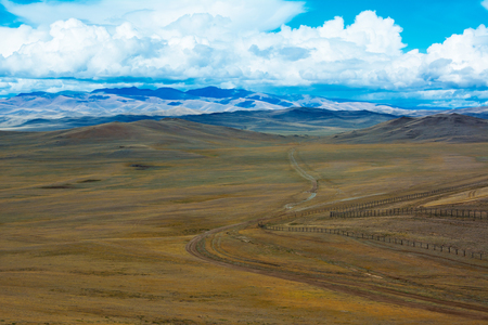 Road stretches into the distance across the steppe, mountains, blue sky with clouds. Chuya Steppe  in the Siberian Altai Mountains, Russia