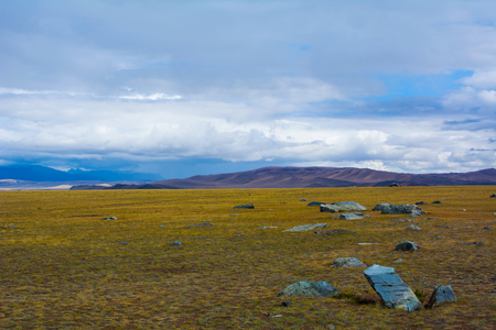 russia steppe: Steppe landscape with large stone in the foreground, mountains view, blue sky with clouds. Chuya Steppe, Kuray steppe in the Siberian Altai Mountains, Russia Stock Photo