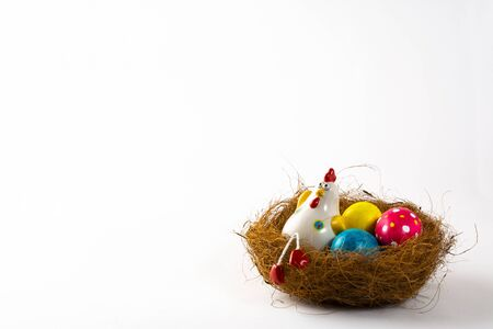 Decorative Hen in a nest with painted Easter eggs on a white background. Easter background. Easter background. Easter symbol. Copy space