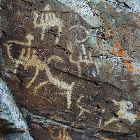 Hunting scenes palaeolithic Petroglyphs carved in rocks. Hunters on camels. Stones with petroglyphs in the Chuya Steppe, Kuray steppe in the Siberian Altai Mountains, Russia