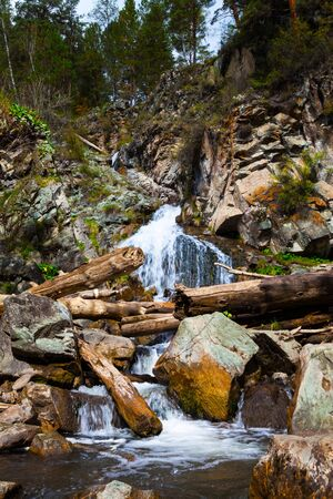Beautiful breathtaking Waterfall in the ro?ks, vertical. Mountain Stream Falls. Mountain stream running over rocks. Altai Mountains Siberia, Russia