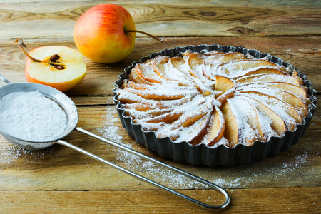 caster: Homemade apple pie, fruit dessert, tart, apples and caster sugar on the wooden table, selective focus Stock Photo