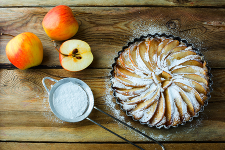 caster: Apple pie, dessert tart with fresh fruits and caster sugar on wooden table, top view