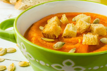 dynia: Dyni squash warzyw zupa z grzankami i pestkami dyni w zielonej miski na białym tle drewnianych, z bliska