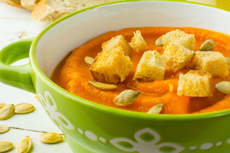 Pumpkin squash vegetable soup with croutons and pumpkin seeds in a green bowl on white wooden background, close up