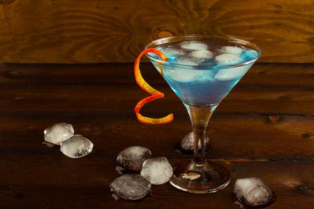 blue hawaiian drink: Blue Martini cocktail on the dark wooden background. Blue cocktail. Blue Martini. Blue Hawaiian cocktail. Blue curacao liqueur.  Blue margarita