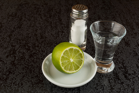 tequila: Silver mexican tequila with lime on black background. Tequila shot Stock Photo