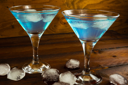 blue lagoon: Two blue cocktails in glasses on dark wooden background. Blue Martini. Blue Hawaiian cocktail